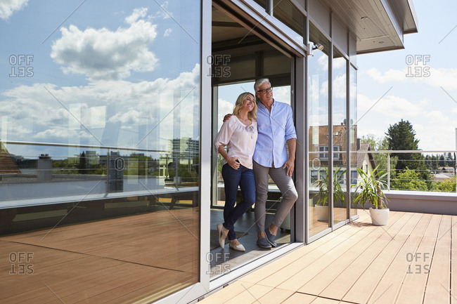 Smiling mature couple standing at roof terrace at home