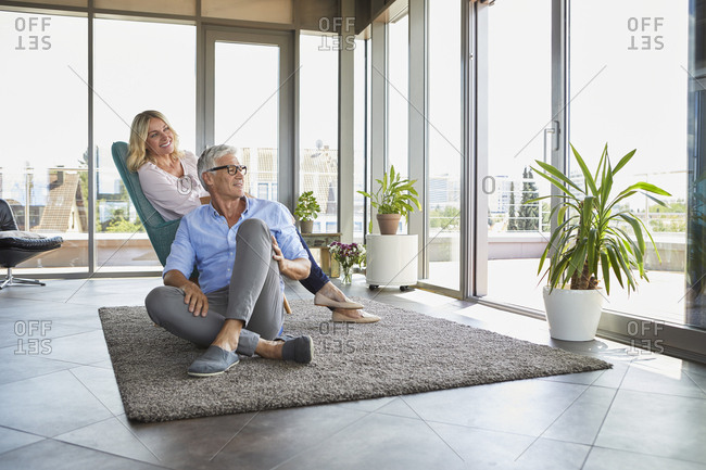 Mature couple relaxing at home looking out of window