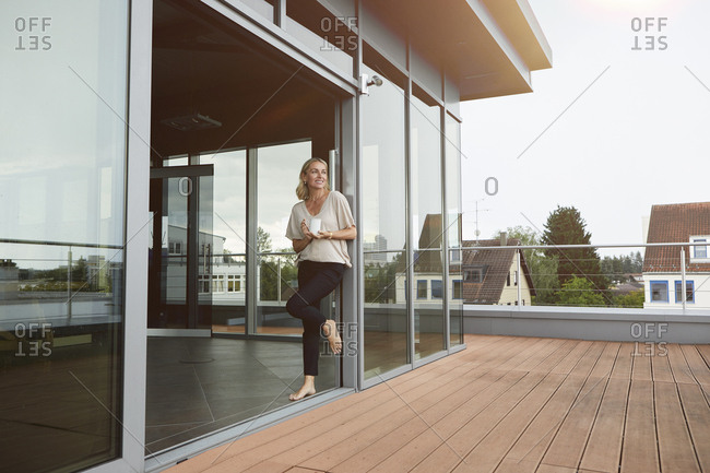 Smiling mature woman with cup of coffee standing at roof terrace at home