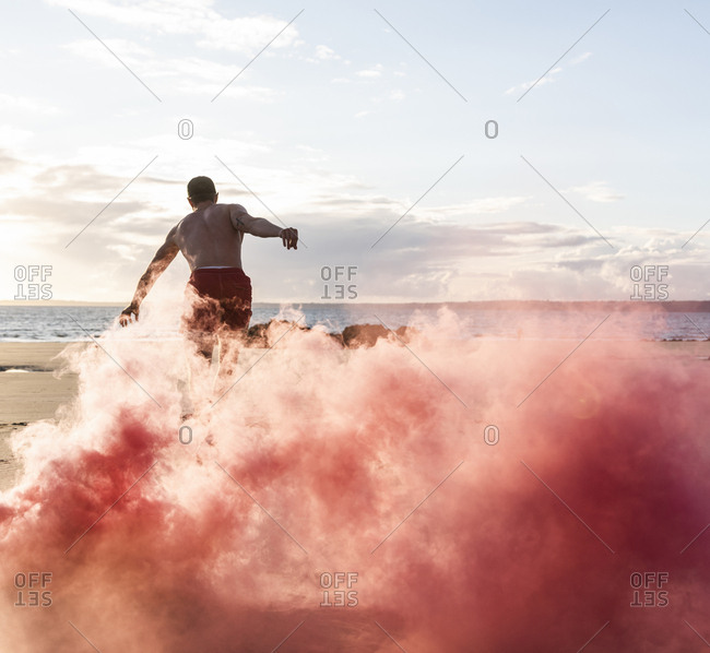 Man doing movement training at the beach with red smoke