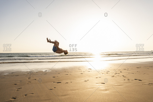 Young man doing somersaults on the beach
