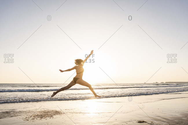 Young woman jumping for joy on the beach