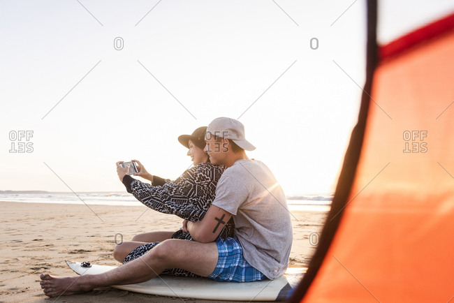 Couple camping on the beach- taking smartphone selfies
