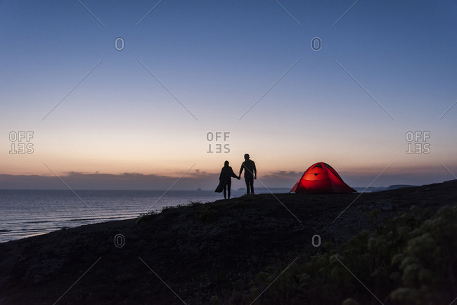 Romantic couple camping on the beach- walking in twilight- holding hands