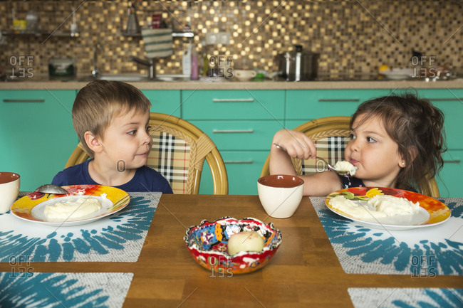 Portrait of boy and his little sister eating breakfast in the kitchen