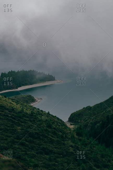 From above view of beautiful pure lake surrounded by mountains with green trees with thick fog above