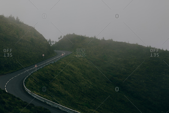 Empty motorway laid on green hill on background of gray sky