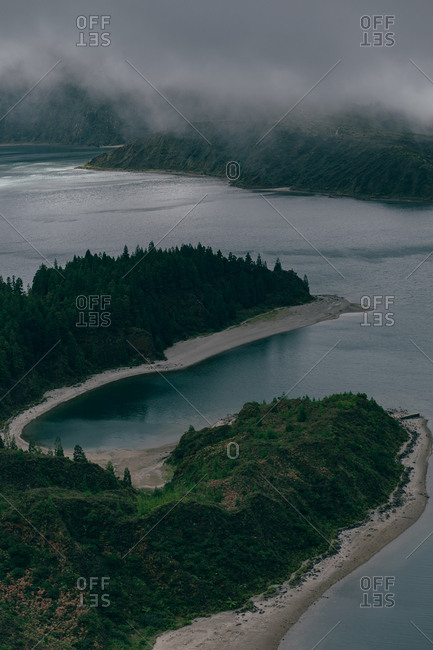 From above view of blue clean lake surrounded by hills with gray fog above