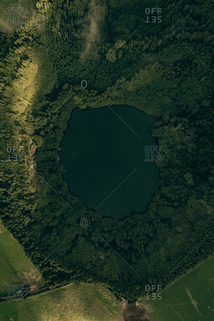Aerial view of little beautiful crater lake surrounded by green plants