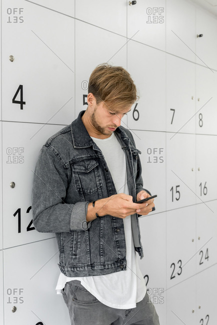 Man Using His Mobile Phone During A Coffee Break In White Coworking Office