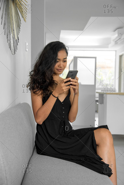 Woman Using His Mobile Phone During A Coffee Break In White Coworking Office