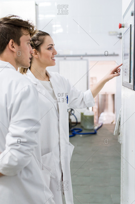 Young man touching machine in a factory and talking with her partner