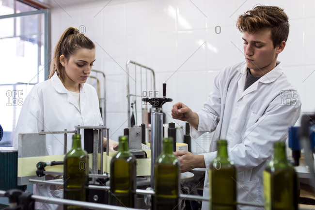 Young woman and young man working in a line production of bottling