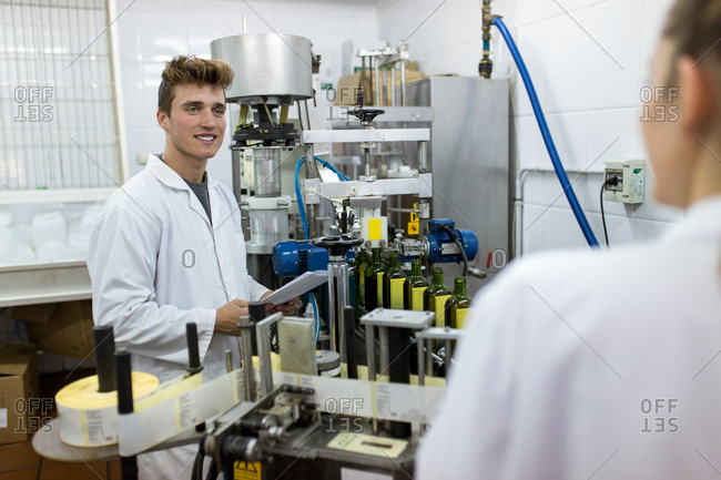 Side view of young caucasian man working in a production line of bottling