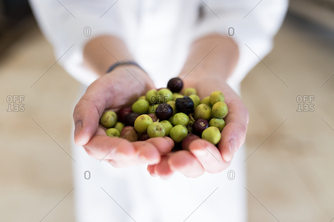 Detail of handful of olives person with white coat background