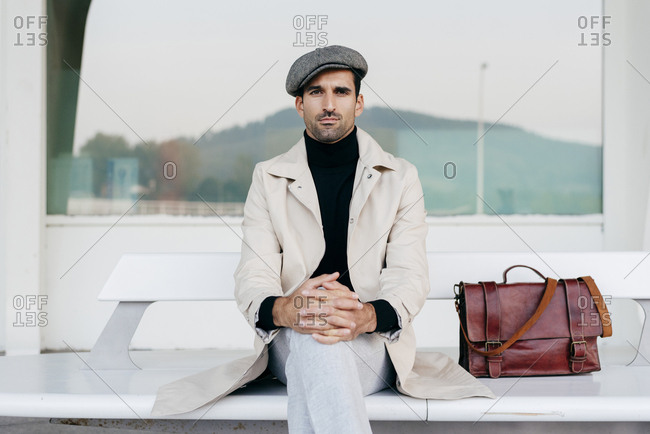 Handsome caucasian man sitting on the bench outside the airport terminal with shoulder bag