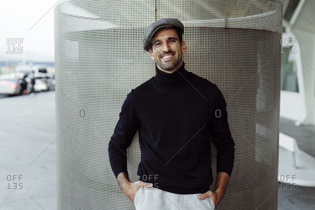 Handsome caucasian man with cap and turtleneck sweater laying on wall and smiling