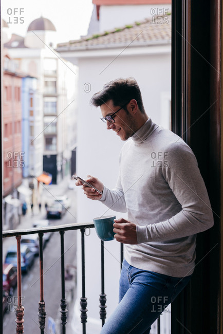 Young caucasian man leaning on balcony using phone and drinking coffee at home