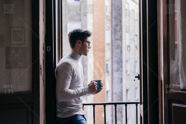 Young caucasian man leaning on balcony and drinking coffee at home