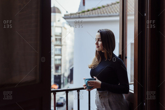 Cute caucasian girl leaning on balcony and drinking coffee at home