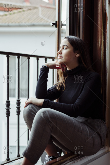 Cute caucasian girl leaning on balcony at home