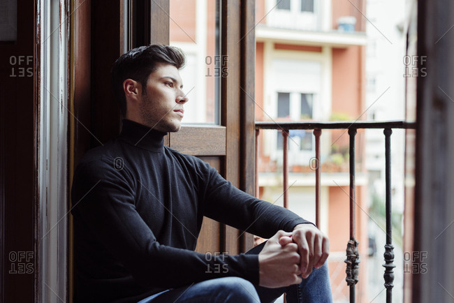 Young caucasian man leaning on balcony at home