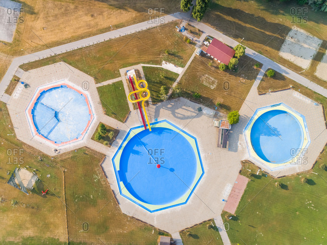 Abstract aerial view of three pools and water slide in abandoned water park.