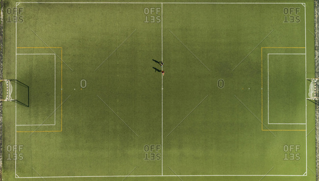 Aerial view of a two players training on synthetic surface football pitch on a summer day.