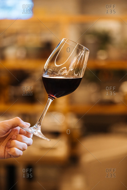 Person holding glass of red wine at an angle