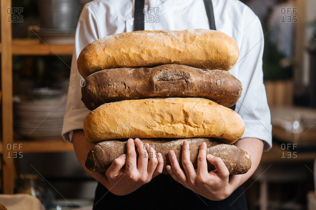 Chef holding stack of fresh baked bread loaves