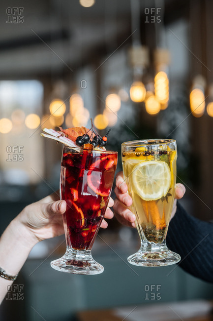 Two people toasting fruity cocktails with berries and lemons