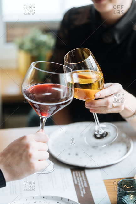 Two people toasting with white and red wine