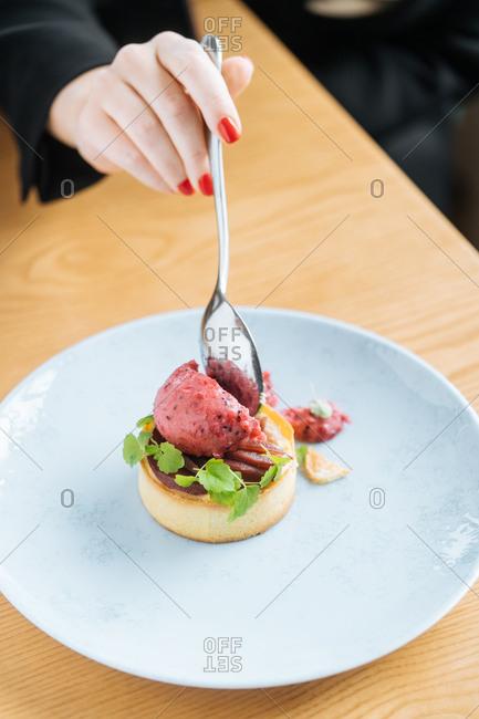 Woman eating gourmet dessert dish
