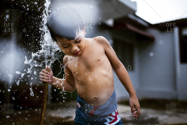 Boy playing in the water from a hose