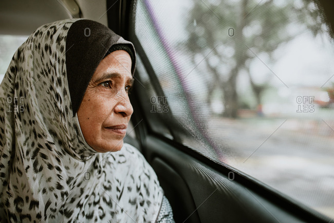 Portrait of Malaysian woman looking out window of car