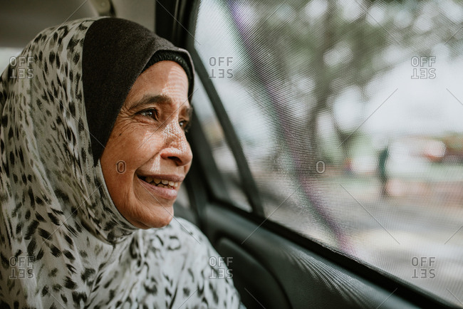 Portrait of smiling Malaysian woman looking out window of car