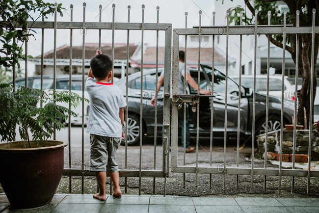 Little boy standing behind gate watching people get into car