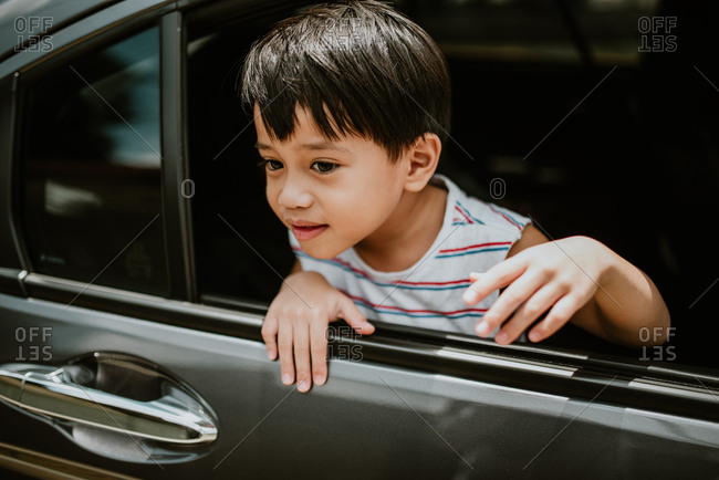 Boy sticking his head out of the open window of a car