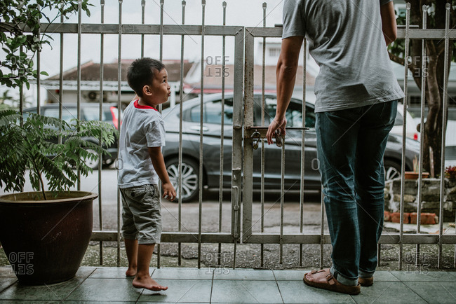 Boy and father standing at gate