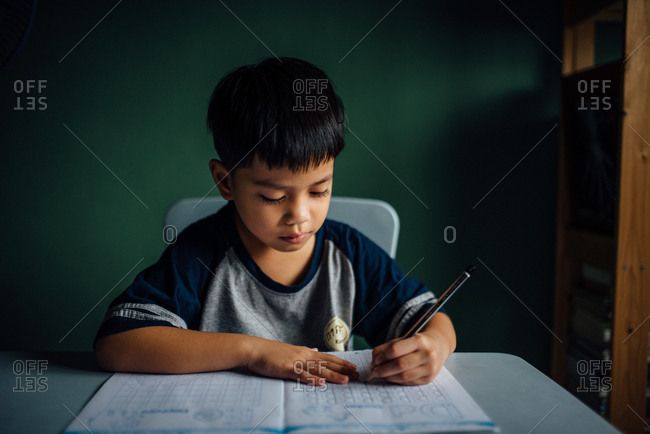 Boy writing letters in workbook