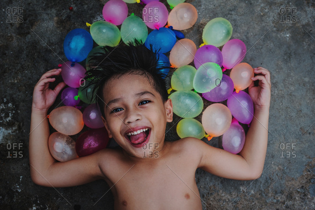 Laughing boy surrounded by colorful water balloons