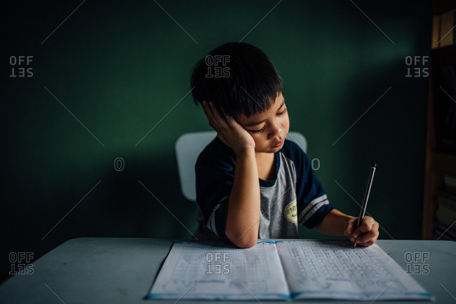 Boy sitting at table doing homework