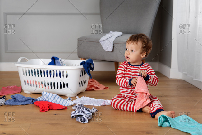 Baby sitting on the floor and playing with the laundry