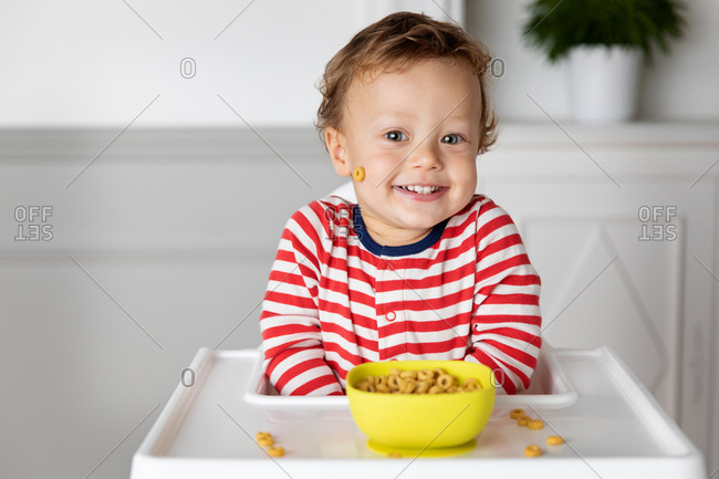Smiling toddler sitting in high chair with a bowl of cereal