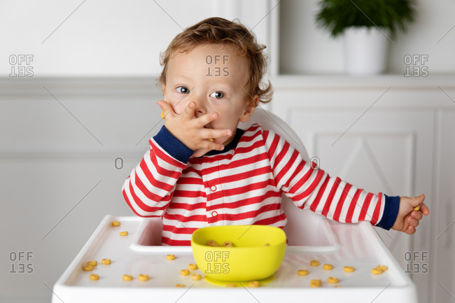 Toddler sitting in high chair eating cereal