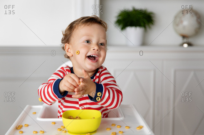 Laughing toddler playing with his food