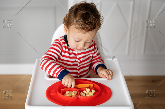 Toddler boy in high chair having a snack