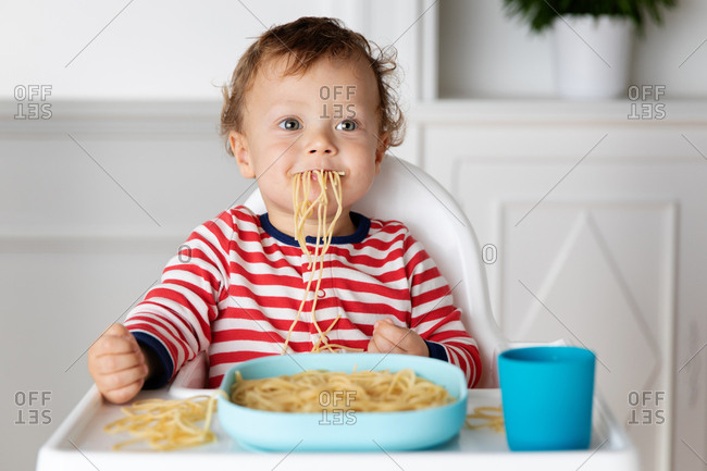 Toddler eating a mouthful of spaghetti noodles