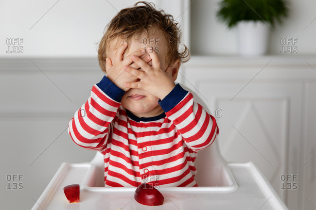 Toddler boy in high chair covering his eyes