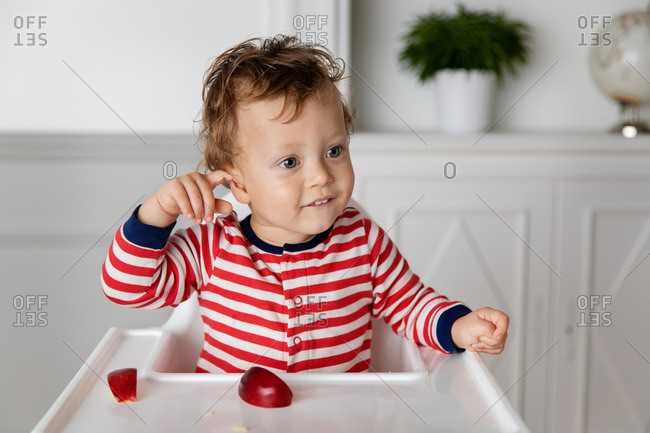 Toddler in high chair with apple slices pointing towards their ear